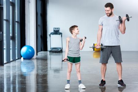 男の子のコーチと一緒にダンベル トレーニング