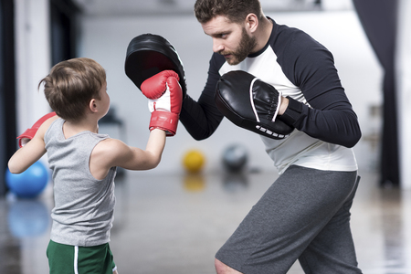 boy boxer practicing punches with coach