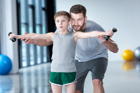 Boy training with dumbbells together with coach