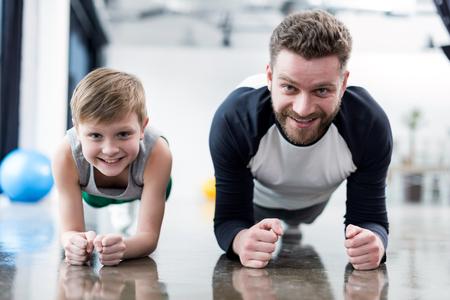 Mens en jongen die plankoefening doen Stockfoto