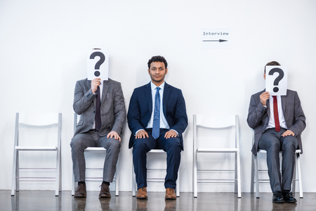 businesspeople sitting in queue and waiting for interview, holding question marks in office Stock fotó