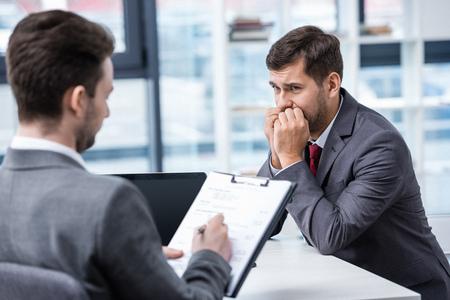 Nervioso hombre en traje formal mirando empresario escribiendo en el portapapeles durante la entrevista de trabajo