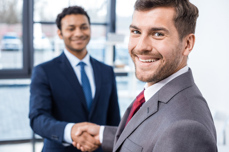 african american handshake: Handsome young businessmen shaking hands and smiling at camera