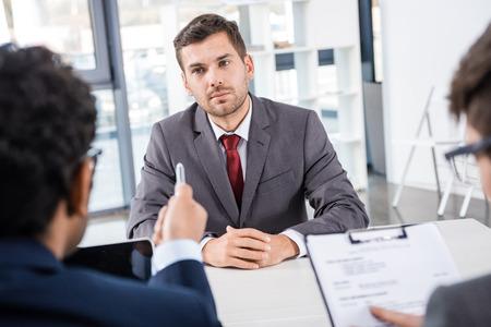aufmerksamer Geschäftsmann, der zu den Kollegen während des Vorstellungsgesprächs hört