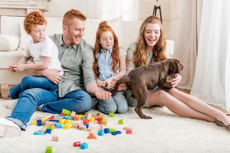 家の床にコンス トラクターと遊ぶ子犬と美しい赤毛家族
