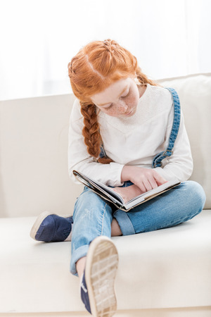 focused little girl reading book while sitting on sofa at home