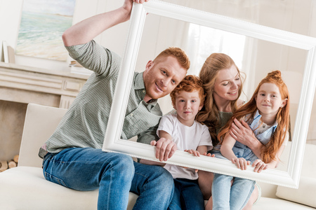 sitt: Beautiful happy redhead family sitting together and looking through white frame