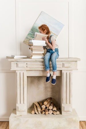 girl reading book while sitting on fireplace