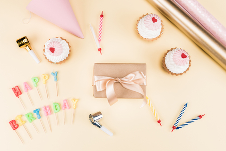 Top view of happy birthday lettering, envelope with ribbon, cakes and colorful cards on pink, birthday party concept