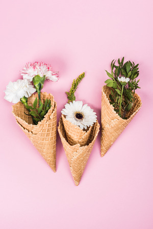top view of flowers in sugar cones with leaves and petals laying on pink table, still life