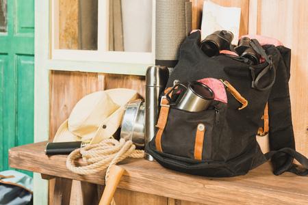 different trekking equipment on bench near wooden house waiting for traveler Stock Photo
