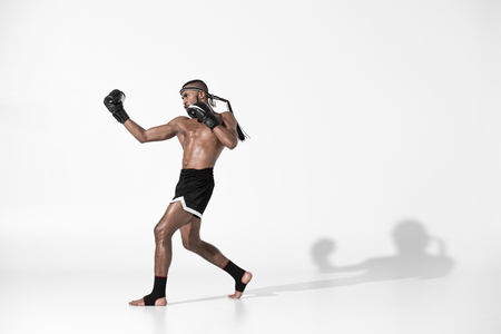side view of muay thai fighter training isolated on white