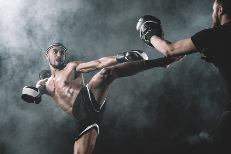 side view of concentrated muay thai fighter practicing kick isolated on black