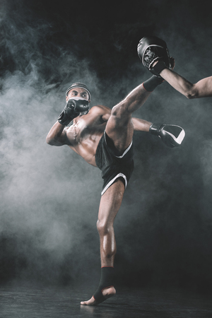 muay thai fighter practicing kick isolated on black