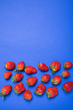 top view of fresh red strawberries isolated on blue with copy space, berries background concept