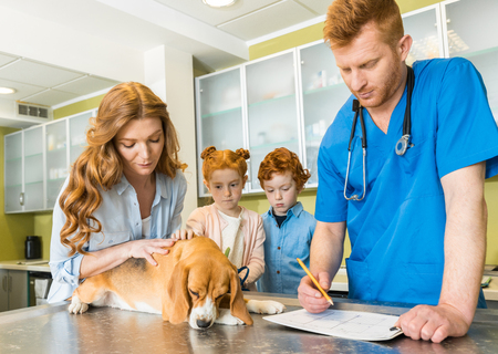 Woman and her children with their dog at veterinary doctor
