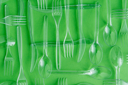 set of various plastic cutlery isolated on green