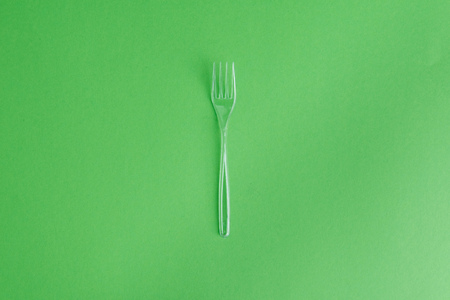 transparent plastic fork isolated on green Stock Photo