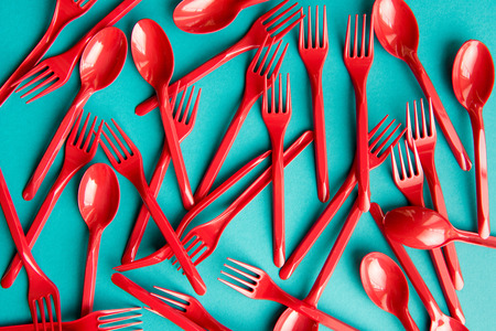set of plastic forks and spoons isolated on blue