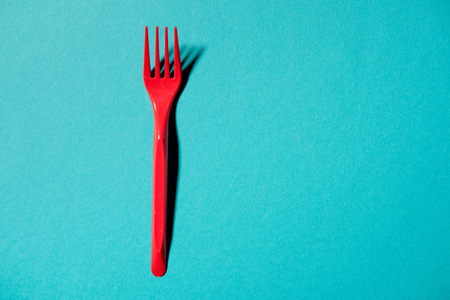 red plastic fork isolated on blue Stock Photo