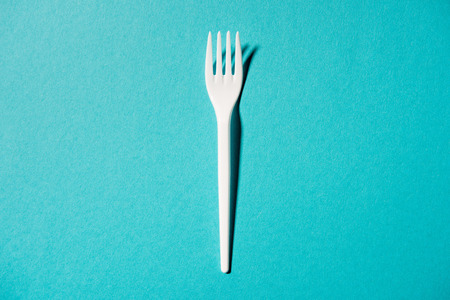 white plastic fork isolated on blue