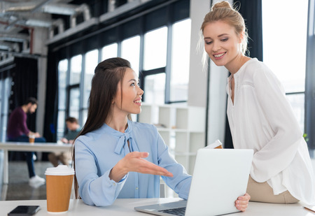 young businesswomen using laptop and talking at workplace