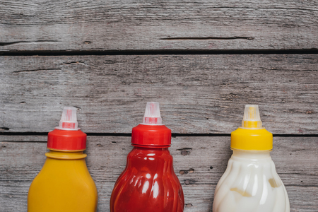 top view on mustard and ketchup with mayo sauces at bottles laying on wooden table