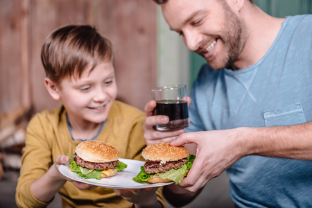 happy father and son holding plate with homemade burgers Stockfoto