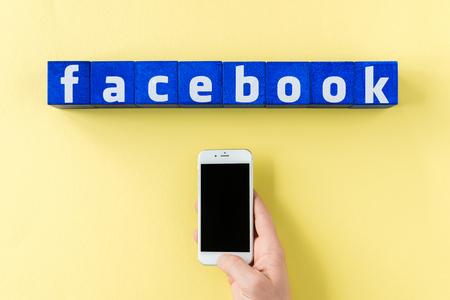 青色キューブとスマート フォンを持っている人間の手から作られた facebook のロゴ