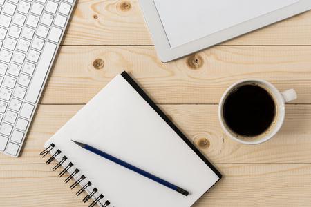 bovenaanzicht van een notebook met een kopje koffie en digitale tablet mock-up