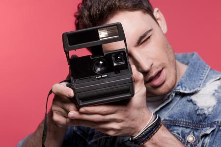 portret van de jonge knappe casual man met vintage camera