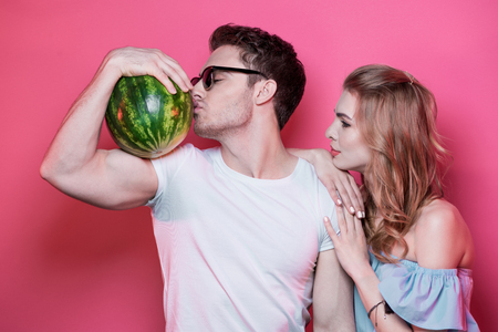 Stylish young couple in love posing with fresh ripe watermelon