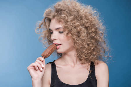 young woman with curly hair eating ice cream isolated on blue