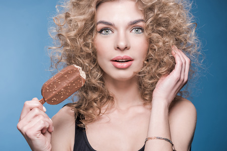 young woman with curly hair holding ice cream and looking at camera Stok Fotoğraf