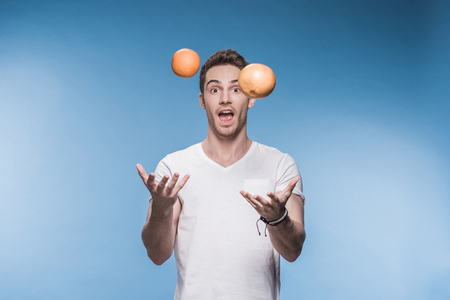 young man juggling with fruits isolated on blue Stock Photo