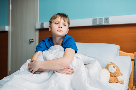 ittle: ittle thoughtful boy sitting on hospital bed