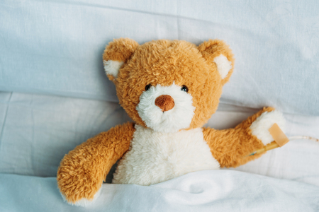 close up view of cute teddy bear toy lying in bed with drop counter Stock Photo