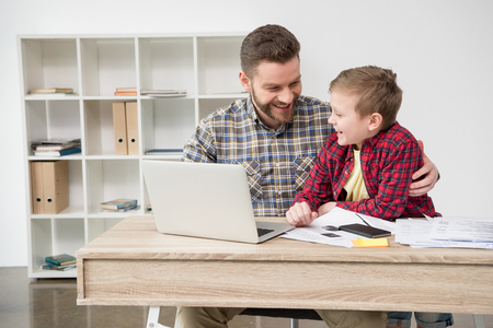 Businessman freelancer working at table with son