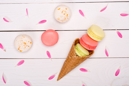 Top view of pink flower petals around of handmade fresh macarons in waffle cone on wooden surface.  sweets background Stock Photo
