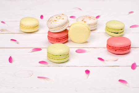 Still life of fresh macarons on the table with pink petals. sweets background concept Stock Photo