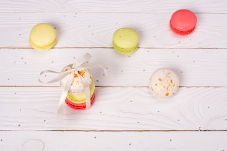 Colorful macarons tying with white ribbon for gift on the table . Fresh macarons background. Stock Photo