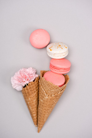 Group of pink macarons styling with waffle cones and flower. Still life of macarons concept Stock Photo