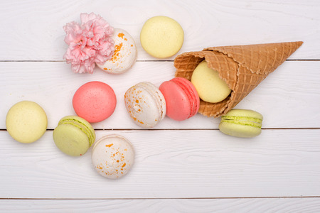 Stack of sweet macaroons and waffle cones styling with flower on wooden surface. sweets background
