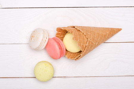 Colorful homemade macarons in waffle cones on wooden surface. sweets background