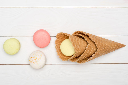 Top view of colorful macaroons in waffle cones on wooden surface. macarons background