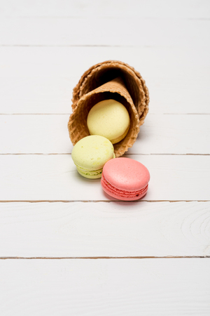 Colorful homemade macaroons in waffle cones on wooden surface. Stock Photo