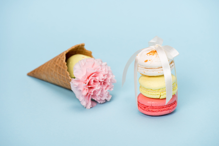 Colorful macarons tying with white ribbon for gift on blue surface. Still life of fresh macarons concept.