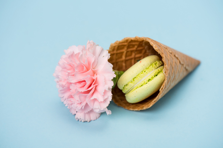 Pistachio macaron with pink flower in waffle cone on blue surface