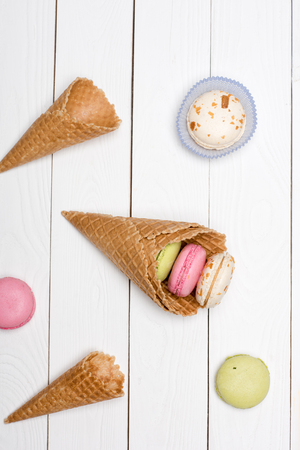 Group of waffle cones and colorful macarons. macarons background