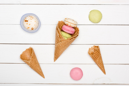 Top view of homemade macarons pattern with waffle cones, sweets background